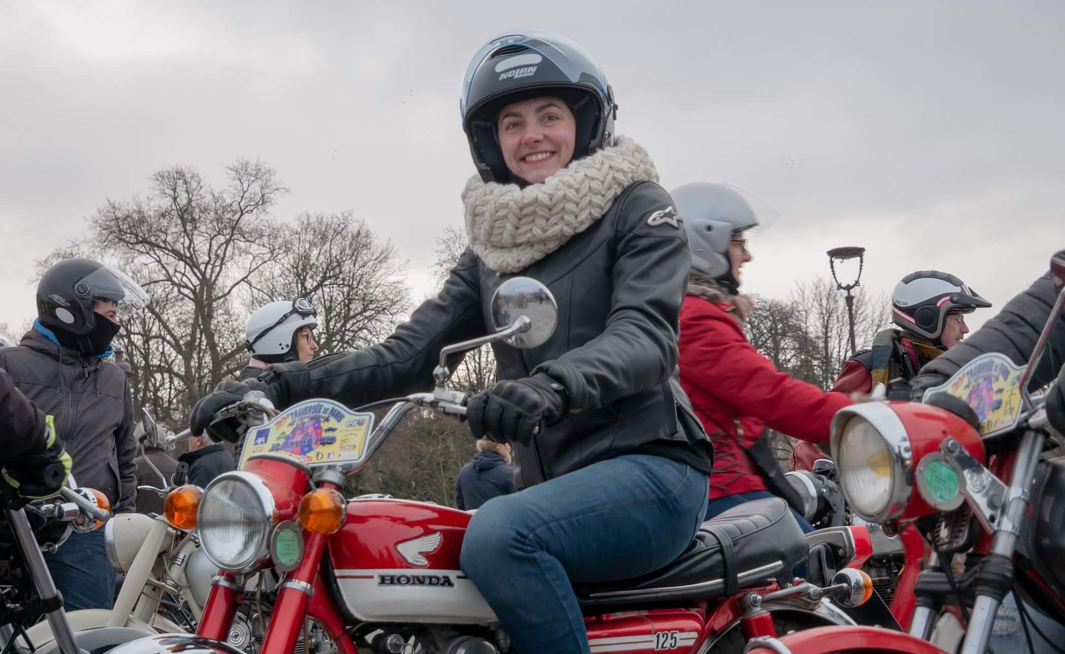 Fille souriant sur une moto honda rouge